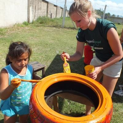 A volunteer painting tyres with children in Argentina on our project for high school students